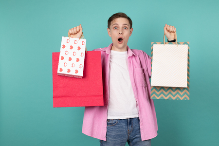 Attractive young man in pink shirt with colorful shopping bags in hands, isolated over blue background