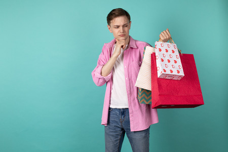 Young attractive man in pink shirt is standing thoughtfully with shopping bags in hand