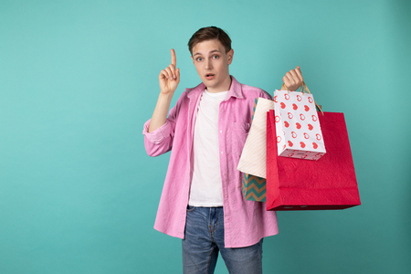 Young handsome man standing thoughtfully with shoping bags in hand