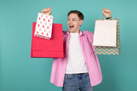 Impressed young man in pink shirt holding colorful shopping bags in hands