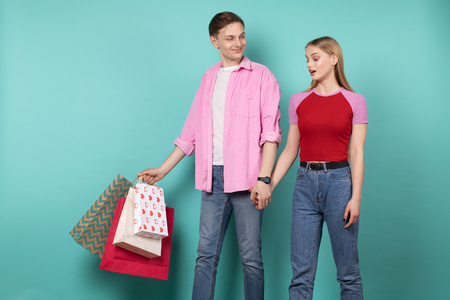 Young romantic couple in casual clothing wallking hand in hand after shopping together