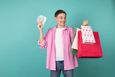 Happy smiling boy in pink shirt with money and shopping backs in hands