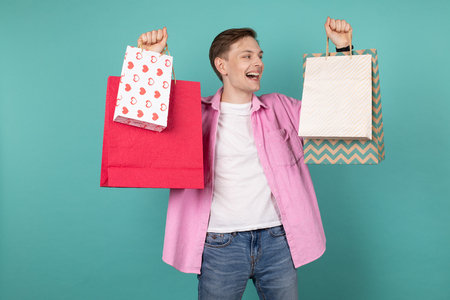 Happy impressed young man in pink shirt holding colorful shopping bags in hands