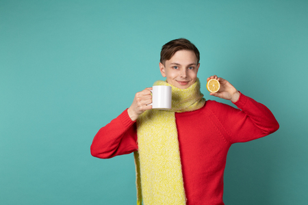 Young attractive man in red sweater and yellow scarf making funny face, holding white cup and sliced lemon in hands