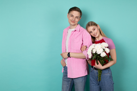 Attractive young man in pink shirt with his girlfriend that leaned on his shoulder