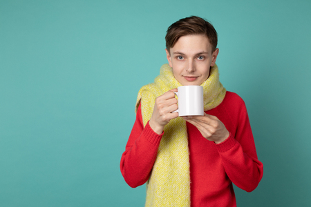Beautiful sensual man wearing red sweater and scarf, holding cup of tea in hand