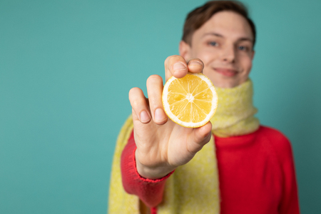 Young handsome man in yellow scarf showing sliced citrus lemon at the camera