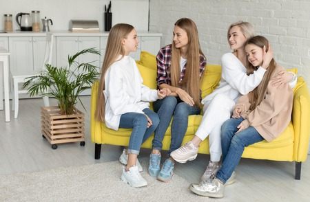 Female lesbian couple with their attractive daughers at home. Lesbian family in casual clothes sitting on yellow sofa Standard-Bild