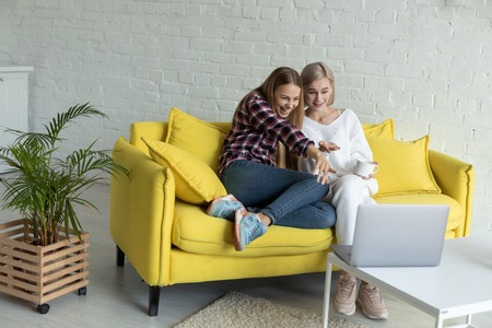 Happy young female lesbian couple in casual clothes sitting together on yellow sofa at home, are watching funny movie on laptop