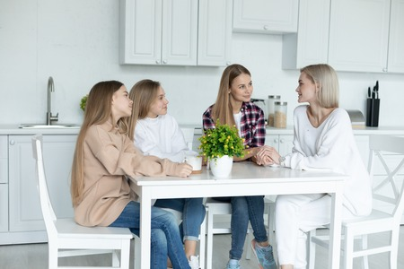 Happy family sitting together in the kitchen at home, all in casual clothes