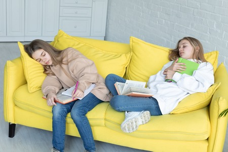 Two little sisters in casual clothes sleeping together on yellow sofa