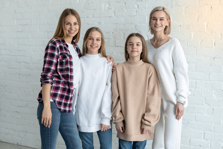 Portrait of beautiful lesbian family in casual clothes, two moms and daughters
