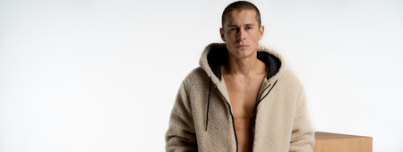 Half length portrait of young handsome male model with short haircut, wearing trendy hoodie, looking at the camera isolated over white background