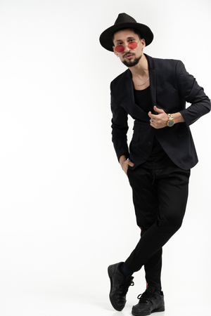 Pleased business man with beard in black suit and hat, in red sunglasses, holding jacket and looking at the camera isolated over white background Stockfoto