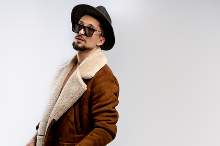 Portrait of young bearded man in black hat and brown coat in black sunglasses isolated over white background, copyspace for your text