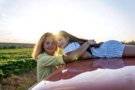 Beautiful smiling family, mom in yellow shirt hugging her dauther in blue striped dress that lies on the roof of the red car, both loooking at the camera, sunset on the background 写真素材