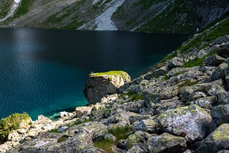 Beautiful panorama, mountain lake with blue water and big stones, summer time