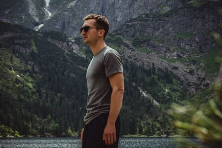 Side view portrait of young man traveler in black sunglasses and grey t-shirt in front of the mountain lake and range, active life concept