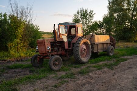 Old red tractor with a tank, barrel sprayer standing near a dirt road Stock Photo