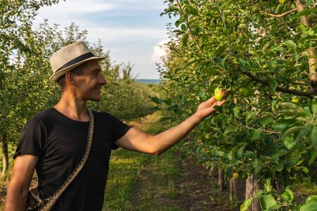 Side view portrait of youn man in hat with shoulder bag standing among the garden and holding apple in hand