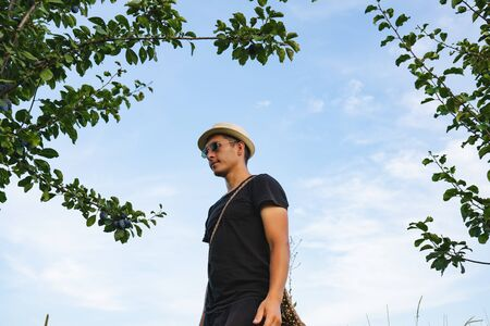 Calmy serious young man in hat and sunglasses standing among branches with green leaves and looking away, blue sky on the background Stockfoto