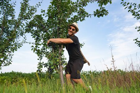 Glad smiling man farmer in hat and sunglasses hugs a plums tree, happy to have a good harvest Stockfoto