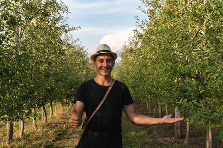 Smiling happy young man in hat wearing black t-shirt standing ampng the apples garden and looking at the camera, showing ok sign with one hand, holding a prodact in other hand