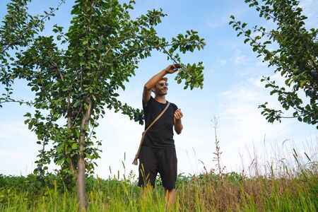 Happy smiling man farmer in white hat and sunglasses standing near a tree holding branch in hand