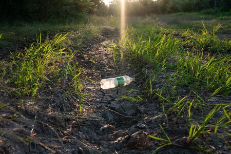 White empty plastic bottle lying on the cracked dry ground Foto de archivo