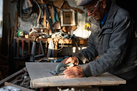 Old senior carpenter in grey clothes and glasses working at home, polishes wood