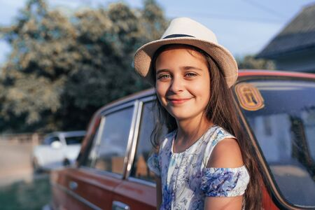Clsose up portrait, beautiful young brunette little girl in dress and hat leaned on the red old antique car and looking at the caamera