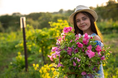 Half length portrait of smiling cute little girl with healthy skin in white hat and dress that holding a large bouquet of pink flowers, landscape on the background