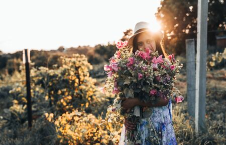 Young girl in white hat and dress covered her face with a large bouquet of beautiful pink flowers, sunset on the background