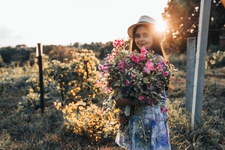 Smiling beautiful little girl in white hat and dress standig with a large bouquet of pink flowers and looking at the camera, sunset on the background Banco de Imagens