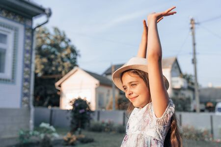 Side view portrait of cute little girl in hat and dress with raised hands, outdoor photo Banco de Imagens