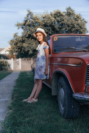 Full length portrait, beautiful young brunette little girl in dress and hat leaned on the red old antique car and looking at the caamera