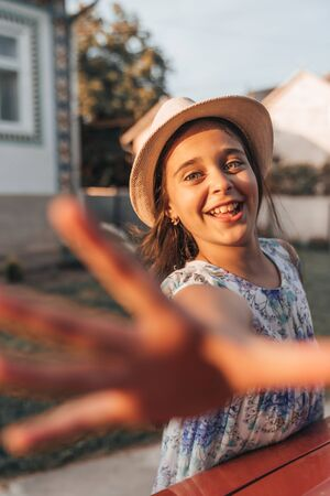 Happy smiling little girl with healthy skinin dress and white hat looking at the camera and reaching for the camera, summer time