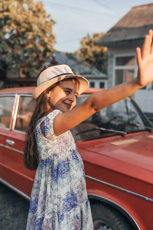 Little cute smiling girl in dress with flowers and white hat standing near red retro car and exetended her hand to cover her face from the sun Banco de Imagens