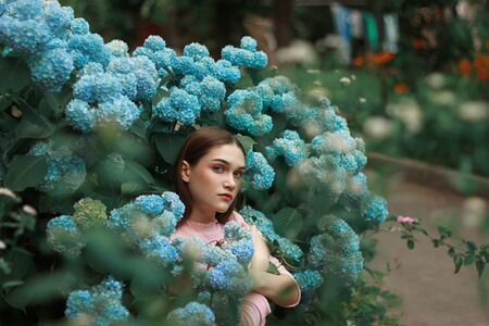 Image of attractive calm girl with brunette hair and bright makeup wearing pink t-shirt, standing among blue flowers and looking at the camera