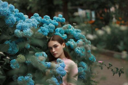 Beautiful brunette girl with red lips and blue eyes standing among blue flowers and looking at the camera Stok Fotoğraf