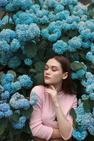Seriously beautiful brunette girl with bright makeup in pink t-shirt among blue flowers, touching her face with hand Stok Fotoğraf