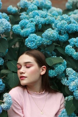 Tender fashion brunette girl with bright makeup wearing pink t-shirt standing among blue flowers with closed eyes
