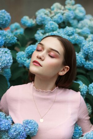 Beauty portrait of young brunette woman with bright makeup, dressed in pink t-shirt standing among blue flowers Stok Fotoğraf