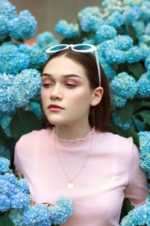 Portrait of young beautiful attractive woman with tender makeup in pink t-shirt, with white sunglasses on her head standing among blue flowers and looking at left down corner