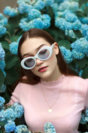 Stylish gorgeous young brunette girl with red lips wearing ping t-shirt and white sunglasses, standing among blue flowers and looking down
