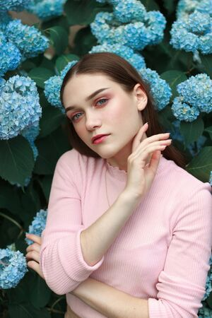 Cheerful beautiful young girl with bright makeup standing among blue flowers and touches her neck with her hand Stok Fotoğraf