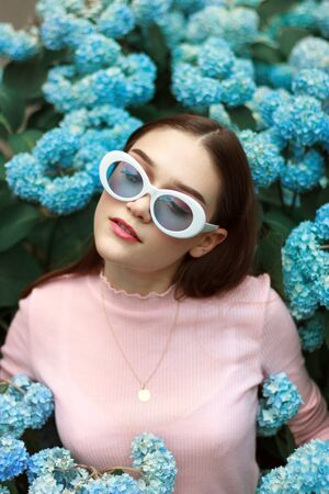 Seriously calm brunette girl in pink t-shirt and white sunglasses among blue flowers