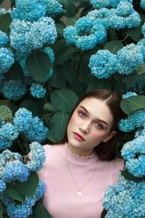 Gorgeous, sexy girl with brunette hair, blue eyes and bright makeup among blue flowers looking at the camera