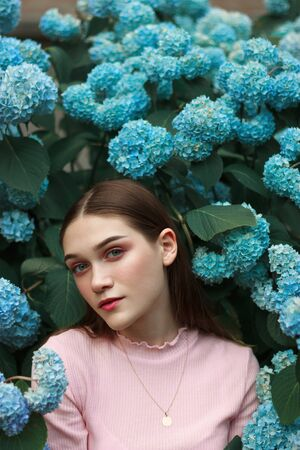 Close up portrait of the beautiful young brunette girl with bright makeup wearing pink t-shirt standing among blue flowers and looking at the camera