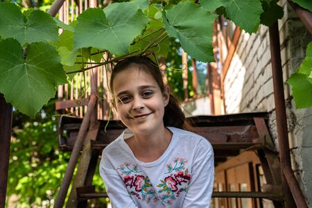 Happy smiling brunette girl in white t-shirt sitting on a metal staircase and looking at the camera, peeking out of vine branches Stock fotó